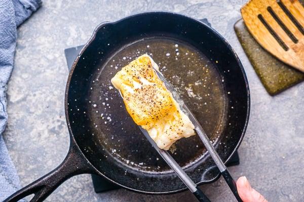 tongs turning pan seared sea bass pan in iron skillet showing seared top of filet