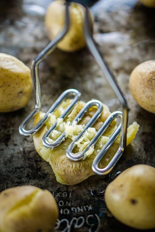 Baby potato on sheet pan being mashed for smashed potatoes recipe