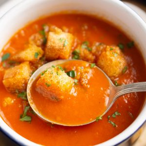 soup spoon lifts tomato soup from white crock topped with croutons and parsley