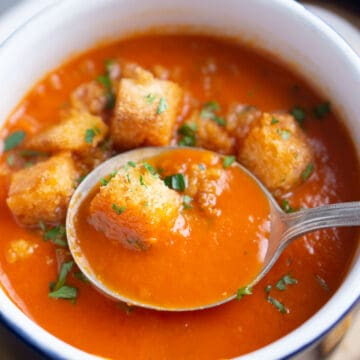 soup spoon lifts tomato soup from blue and white crock topped with croutons and parsley